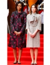 ميشيل اوباما في معطف مزهر من الجاكار ضارب للحمرة من ثاكون عند مقابلتها سيدة فرنسا الاولى كارلا بروني ساركوزي السيدة الاولى في فرنسا