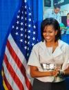 ميشيل أوباما في معطف اكمامه بشكل الجرس مع حزام من جيفنشي خلال محاضرة في مركز للرعاية الصحية