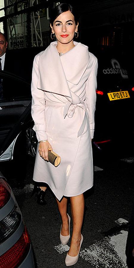 كاميلا بيل,في معطف كريمي مع ربطة عنق عند مستوى الخصر وشال على الرقبة مع حذاء جلدي انيق