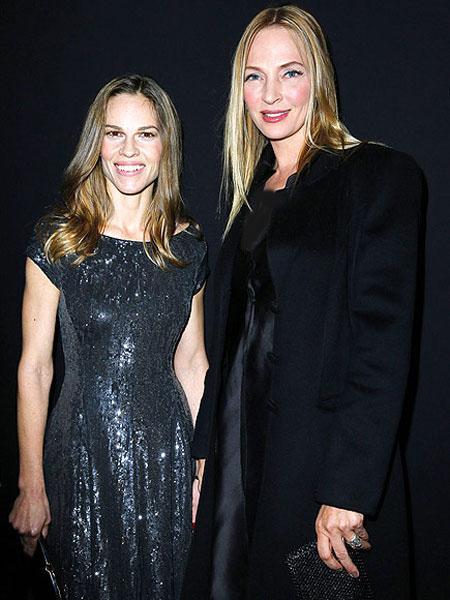 اوما ثورمان وهيلاري سوانك,في ملابس لامعة وحريرية,النجمتين جلستا في الصف الامامي عند مشاركتهما في حضور عرض جورجيو ارماني بريف في باريس.