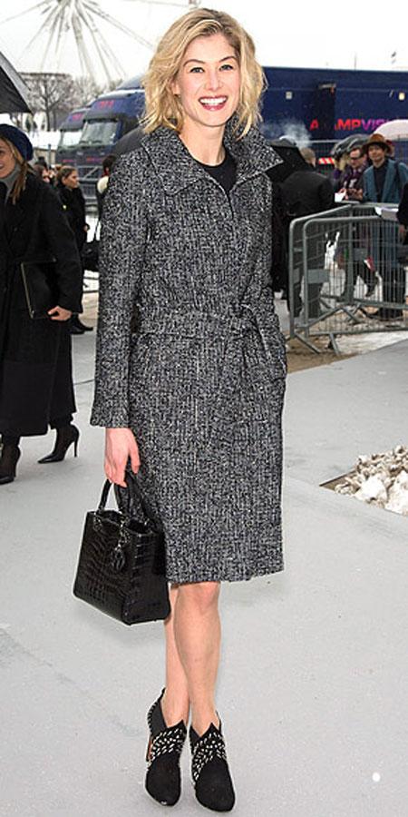 روزاموند بايك,ارتدت ثياب جميلة معطف من الصوف والموهير من ديورعند ذهابها لحضور عرض ديور