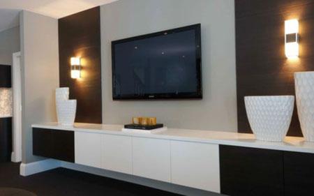 جدار TV مع خزانة للتخزين اسفل منه وشمعدانات على جانبي الحائط.